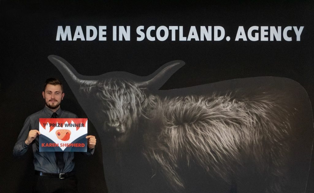 Adam holding 1st prize winner of cheeky coo competition